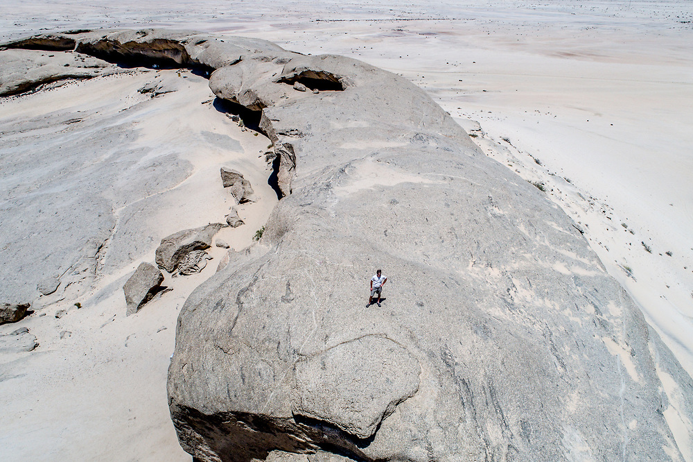 View of a man standing on Vogelfederberg rock formation  in Namibia, Africa.