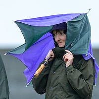 A supporter shelters from the rain at the Camogire Final held in Clarecastle on Saturday