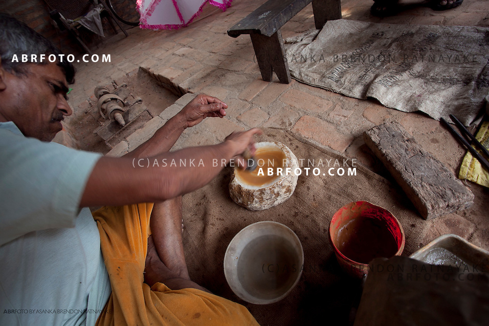 Mr Gunasoma, grinding the lense to get the right curvature in a special grinding stone selected from a series of such grinding stones with different curvatures.