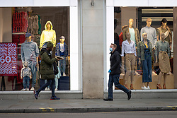 © Licensed to London News Pictures. 19/03/2020. London, UK. A man wearing a face mask and protective gloves (R) and man eating a slice of pizza pass each other in Picadilly Circus as the Coronavirus outbreak continues to escalate in London. The government has announced a series of measures designed to slow the spread of the virus, which is now spreading more rapidly in the capital than in other parts of the country. Photo credit: Rob Pinney/LNP