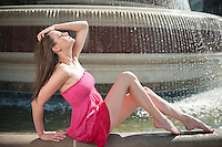 Side view of beautiful young woman in pink dress sitting by water fountain