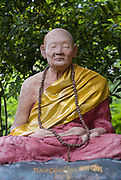 Seated monk, sculpture, temple, Northern Thailand.