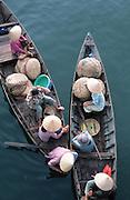 April 2002 - Hoi An, Vietnam - Vietnamese women take a break on their way to a nearby morning fish market. Photo Credit: Luke Duggleby
