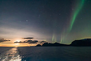 A dim but photogenic aurora on November 7, from the coast of Norway on the Hurtigruten ship the m/s Nordlys, in a view looking east and south to Auriga and Perseus and with the waning Moon rising astern of the ship. <br /> <br /> This is a single 1-second exposure with the Sigma 14mm Art lens at f/1.8 and Nikon D750 at ISO 6400.