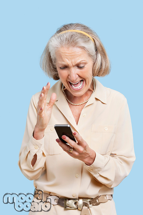 Irritated senior woman reading text message on cell phone against blue background