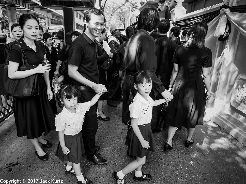 26 OCTOBER 2017 - BANGKOK, THAILAND:  People line up in front of a temple in Bangkok to make an offering for the late king during the funeral ceremony for Bhumibol Adulyadej, the Late King of Thailand. The king died on 13 October 2016 and was cremated 26 October 2017, after a mourning period of just over one year. The revered monarch was the longest reigning king in Thai history and is credited with guiding Thailand through the turbulent latter half of the 20th century.       PHOTO BY JACK KURTZ