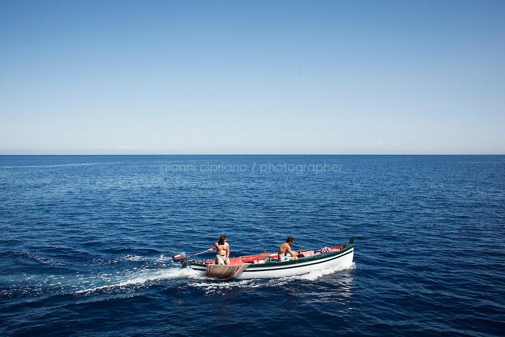 STROMBOLI (ME), ITALIA - 14 GIUGNO 2013: Due uomini su una barca navigano nei pressi del moldo di Stromboli il 14 giugno 2013.<br /> <br /> Karol Hoffman, che vive da 30 anni insieme ad altri connazionali a Ginostra, considerato che il governo nazionale non ha mai provveduto a risolvere il problema di una centrale fotovoltaica malfunzionante, ha lanciato un appello alla Cancelliera Angela Merkel.