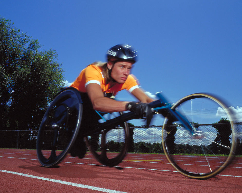 Young man races wheelchair on track