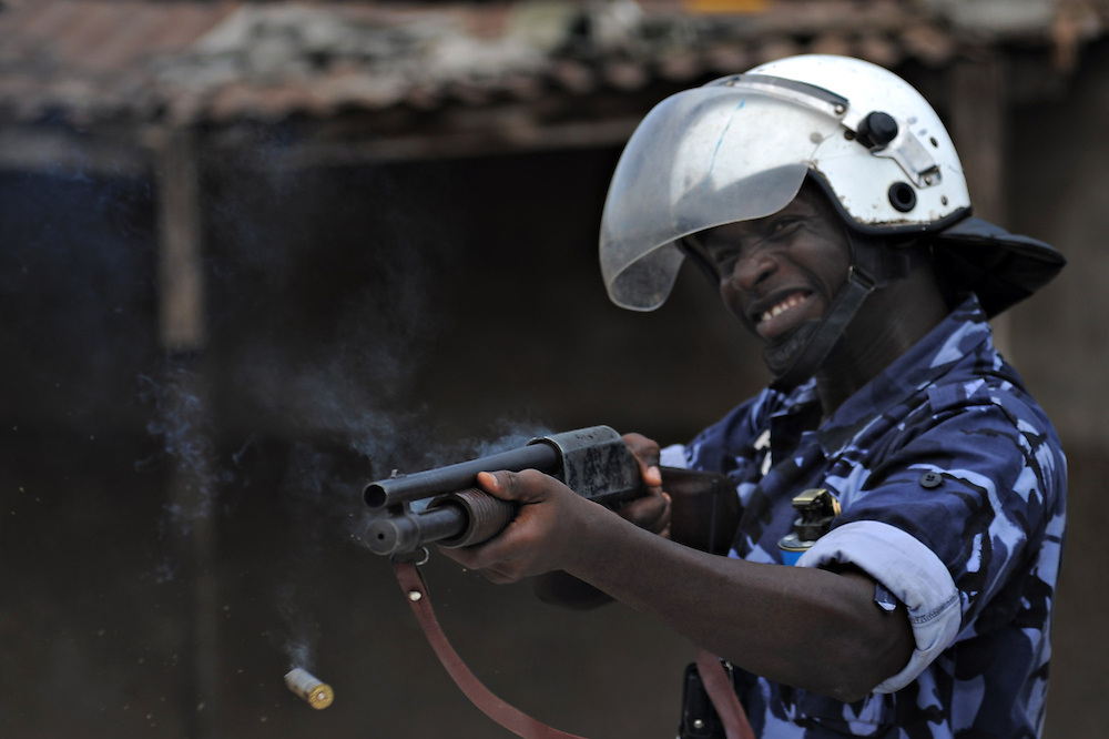 LOME, TOGO - 12-10-05   -  A Gendarme fires at protesters in the Lomé neighbourhood of Bé.  A peaceful protest was scheduled by opposition groups, but their route was blocked by police.  For months, opposition parties have been calling for the departure of president Faure Gnassingbe, whose family has been in power for over 40 years.   Photo by Daniel Hayduk