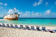 Tourists and a beached ship rest at Governor's Beach on Grand Turk, in the Turks and Caicos Islands.