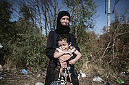 Gevgelija, Macedonia - A woman with her child, minutes after she has crossed the Greek - Macedonian border, on the 23rd of August 2015. Thousands of refugees (mostly coming from Syria) and immigrants try every day to cross the Greek border to Macedonia (Fyrom), hoping to continue their journey to Central/North Europe and eventualy reach countries like Germany, Great Britain and Sweden.