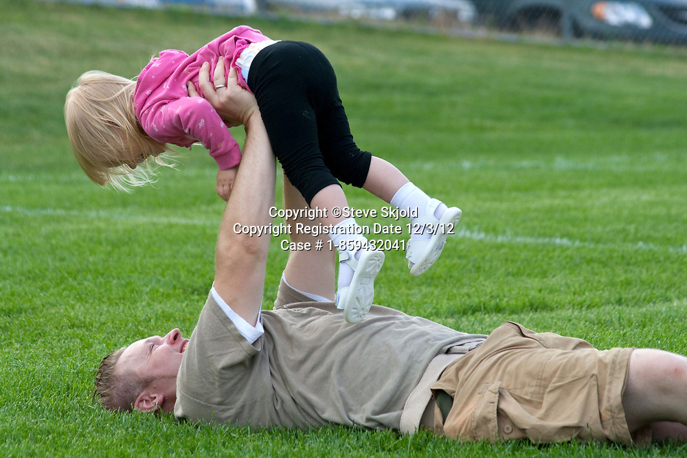 Dad playing with daughter in the park ages 35 and 2. Carondelet Field by Expo School St Paul Minnesota MN USA