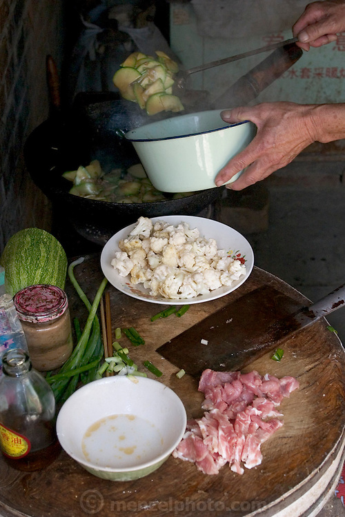Preparing a lunch of squash, cauliflower, mushrooms and green onions at the Cuis of Weitaiwu village, Beijing Province. The round chopping block is made from a slice of tree trunk, a common practice in China. (Supporting image from the project Hungry Planet: What the World Eats.)