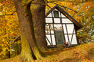 A young family sat in front of a picturesque house surrounded by flora and fauna in autumn near Copenhagen.
