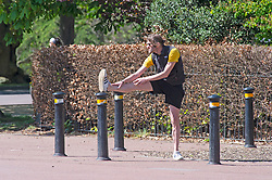 ©Licensed to London News Pictures 14/04/2020  <br /> Greenwich, UK. A man stretching before a run. Sunny weather in Greenwich park, Greenwich, London as people get out of the house from coronavirus lockdown to exercise. Photo credit:Grant Falvey/LNP