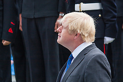 London, June 23rd 2014. Mayor Boris Lohnson watches the flag being raised at City Hall as members and veterans of the armed forces gather for a flag raising ceremony to mark Armed Forces Day