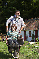 Father pushing son (7-9) in wheelbarrow outside cottage portrait