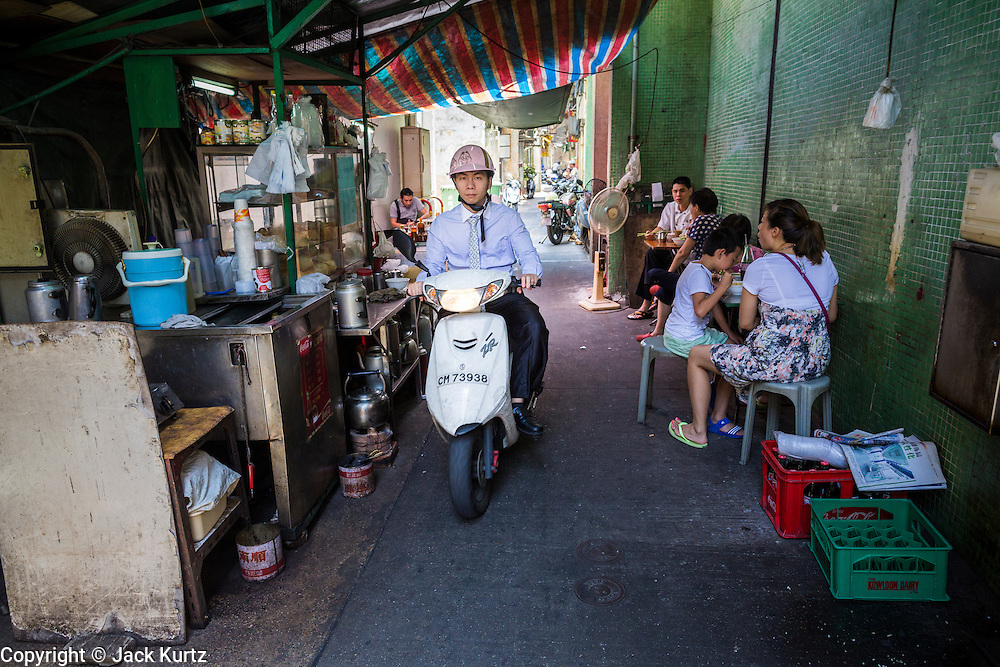 12 AUGUST 2013 - MACAU: A man rides a motorcycle between street food stalls in Macau. Macau, also spelled Macao, is one of the two special administrative regions of the People's Republic of China (PRC), the other being Hong Kong. Macau lies on the western side of the Pearl River Delta across from Hong Kong to the east, bordered by Guangdong province to the north and facing the South China Sea to the east and south. The territory's economy is heavily dependent on gambling and tourism, but also includes manufacturing.     PHOTO BY JACK KURTZ
