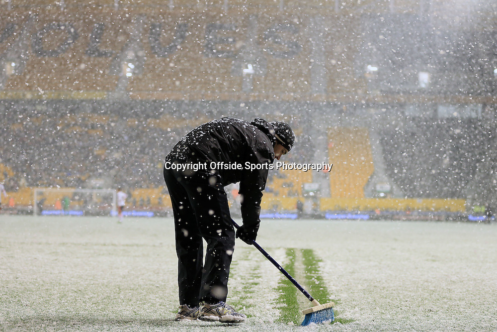 13th January 2015 - FA Cup - 3rd Round Replay - Wolverhampton Wanderers v Fulham - A groundsman sweeps snow away from the pitch - Photo: Simon Stacpoole / Offside.