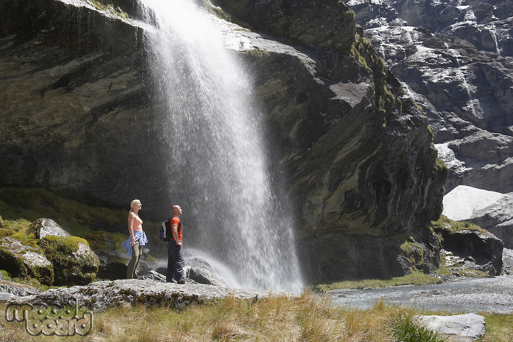 Hikers standing under waterfall at river