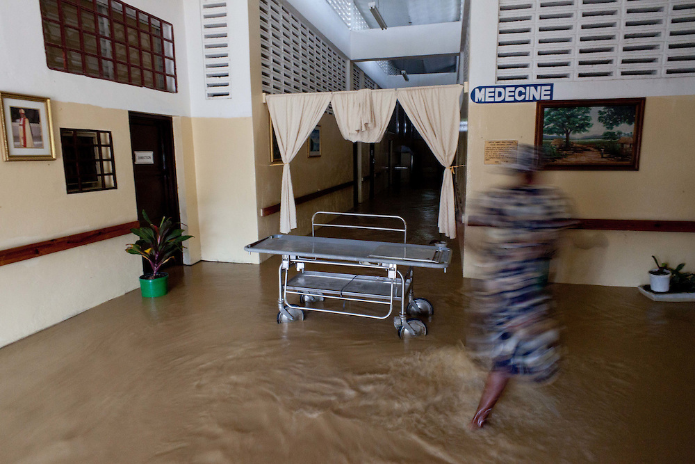 A woman walks through a hospital flooding from rain from Hurricane Tomas. The flooding started early in the morning and the patients were all moved to the second floor.