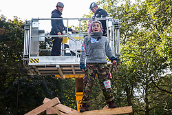 London, UK. 9 October, 2019. A climate activist from Extinction Rebellion feigns horror as police officers on a JCB cherry picker approach from behind to try to arrest her after she had climbed on top of a wooden structure to block Birdcage Walk on the third day of International Rebellion protests.