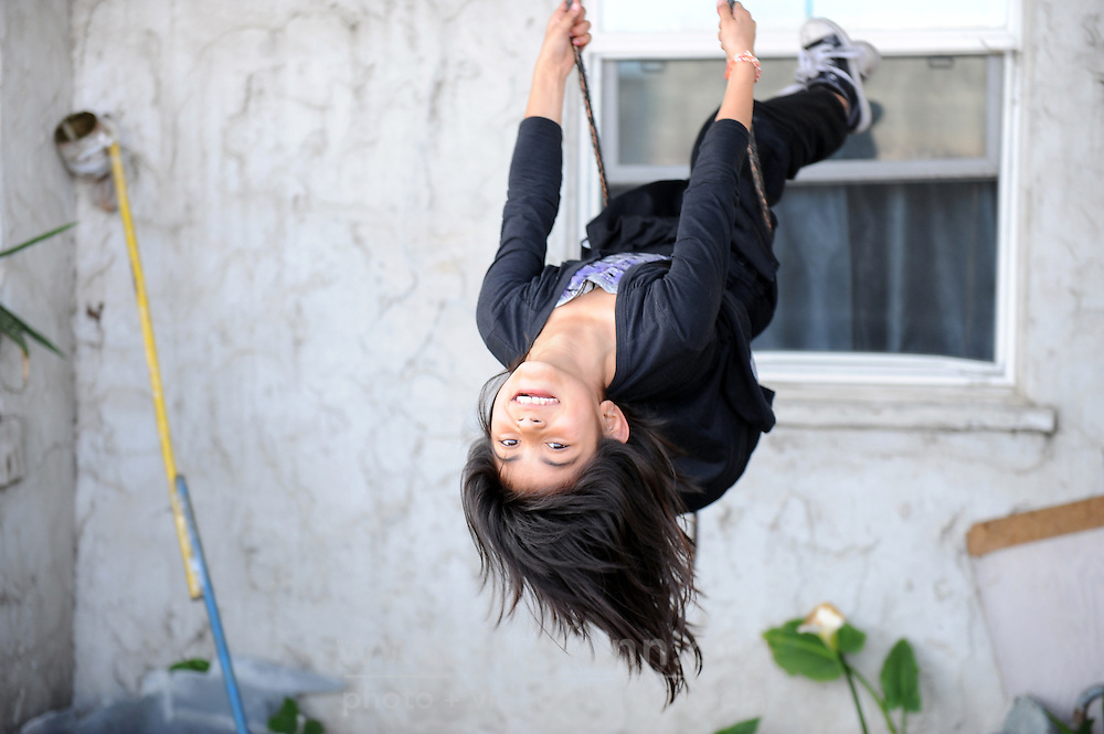 Just hanging out after school, eight year-old Mairin Chavez plays on a solitary rope hanging from a tree in her modest front yard in east Salinas. Keen to show off her gymnastic skills, she twisted and turned for a visitor all kinds of different ways, just for fun.