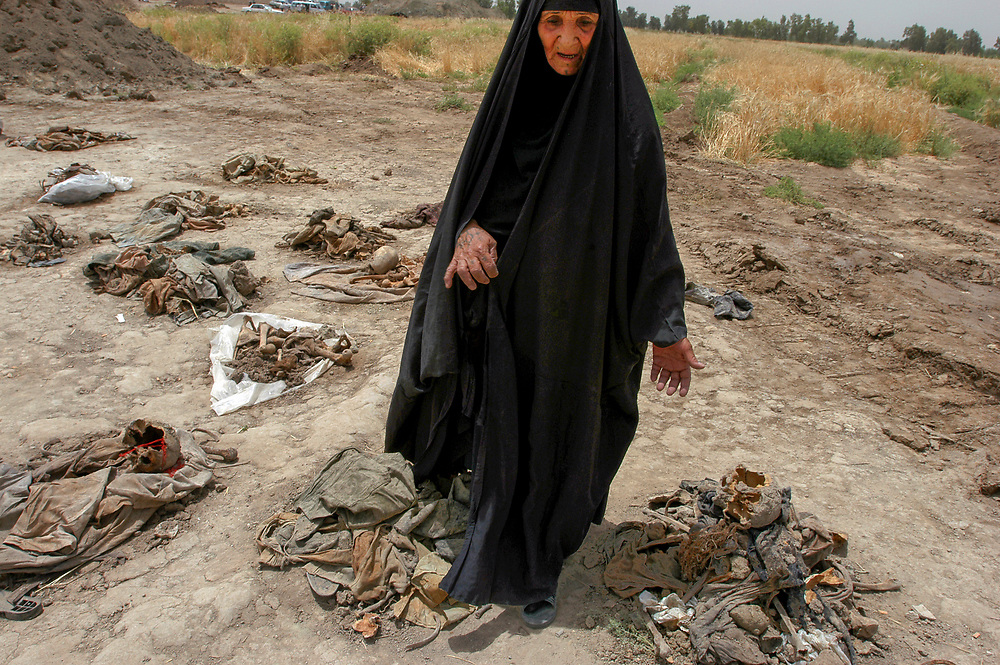 A woman seeks missing family at a mass grave thought to contain 10 to 15 thousand victims of Saddam Hussein's regime. The site was uncovered 20 kms north of the town of Hilla.  <br /> Mahwheel, Iraq. 15/05/2003.