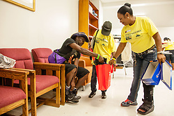 Kenneth Warner, left, finds a new pair of shoes with volunteer Yvette Henry.  Project Homeless Connect  connects those in need of support with vital resources and services.  St. Thomas, USVI.  4 December 2015.  © Aisha-Zakiya Boyd
