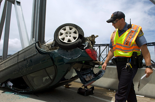 Officer Leon Kennedy of the Vicksburg Police Department examines a flipped car on the westbound lane of the Mississippi River Bridge on Wednesday, June 22, 2011. The car flipped after it was rear-ended by a semi-trailer while crossing the bridge, slowing and eventually shutting down westbound traffic. (Bryant Hawkins/The Vicksburg Post)