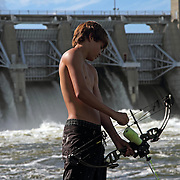 McKinnon Bell, 14, from Indianola, loads an arrow in his crossbow as he prepares to snare a fish in the Des Moines River, east of the Red Rock dam last July.  photo by david peterson