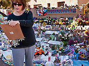"15 JANUARY 2010 - TUCSON, AZ:    A woman writes a note for Congresswoman Gabrielle Giffords in front of a memorial at Giffords' office in Tucson, AZ, Saturday, January 15. Six people were killed and 14 injured in the shooting spree at a ""Congress on Your Corner"" event hosted by Arizona Congresswoman Gabrielle Giffords at a Safeway grocery store in north Tucson on January 8. Congresswoman Giffords, the intended target of the attack, was shot in the head and seriously injured in the attack but is recovering. Doctors announced that they removed her breathing tube Saturday, one week after the attack. The alleged gunman, Jared Lee Loughner, was wrestled to the ground by bystanders when he stopped shooting to reload the Glock 19 semi-automatic pistol. Loughner is currently in federal custody at a medium security prison near Phoenix.PHOTO BY JACK KURTZ"