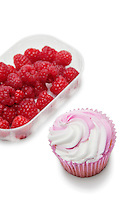 Cupcake with raspberries in container over white background
