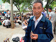 Man with pipe at bird market, Duyun, Guizhou Province, China.