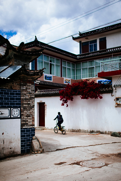A man rides a bicycle through a small village in Dali, China.