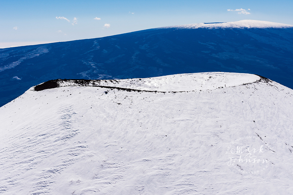 Snow covered cinder cone on the summit of Mauna Kea, Big Island (Hawaii Island), Hawaii. Mauna Loa volcano is seen in the distance.