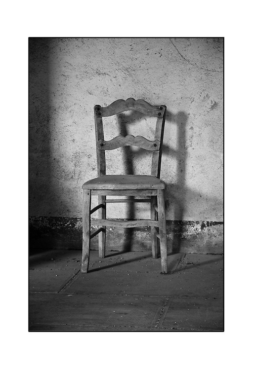 Black and white print of an old wooden chair against a wall in France.