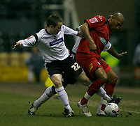 Matt Oakley (left) tackles Colchester sub Chris Iwelumo (right)