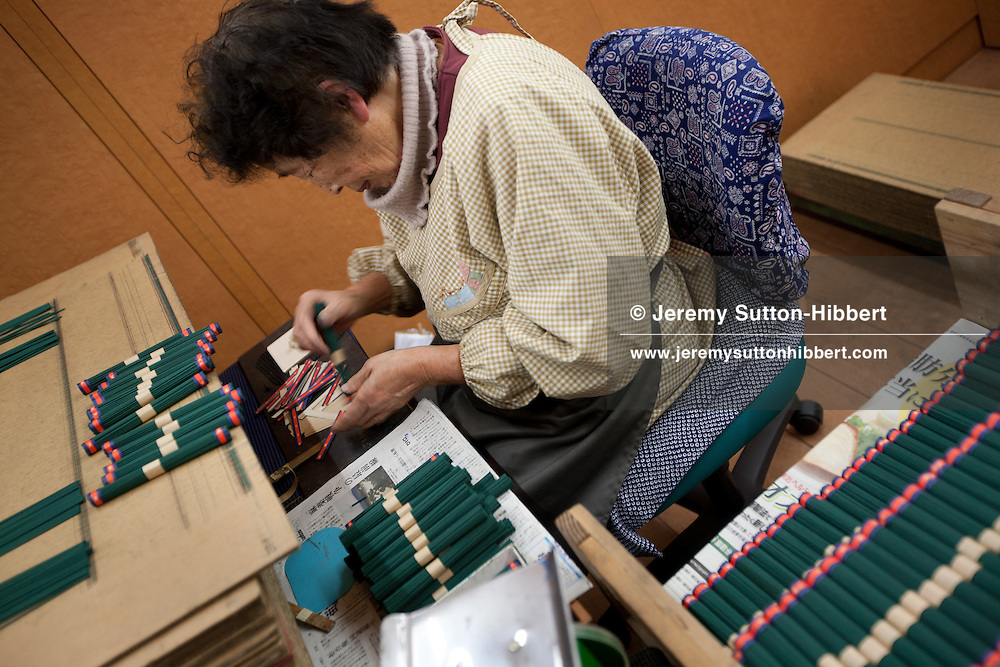 Elder women work bundling, and sealing with tape, sticks of incense during production at the Keigado Co. Ltd. incense manufacturers, part of the Awaji island Koh-shi group/cooperative of incense manufacturers, at Ei Awaji city, Awajishima, Japan, on Thursday 12th January 2012.