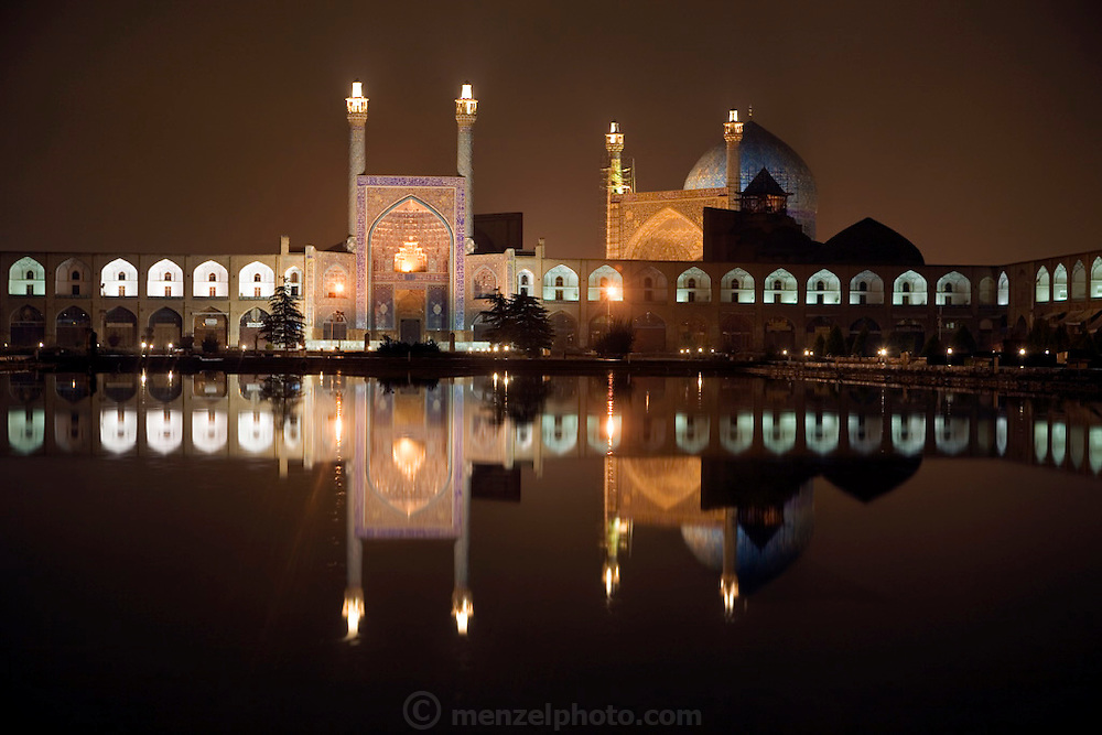 View of the magnificently tiled Masjed-e Imam (Royal Mosque) and its reflection at night in Imam Square, Isfahan, Iran. (Also referred to as Emam Square). Built by the Safavid ruler, Shah Abbas 1, as part of the renovation of the central square of Isfahan. The architect was Ostad Abu'l-Qasim.  (Imam Square is also called Naghsh-i Jahan Square).