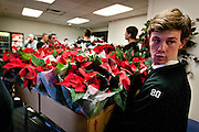 Cottonwood High School baseball player Doug Orchard unloads a crate of poinsettias to deliver to veterans at the George E. Wahlen Department of Veterans Affairs Medical Center, Wednesday, Dec. 5, 2012.