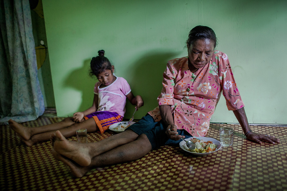 Mama Yuli eats lunch with her granddaughter, Anace (8). They are very close. In 2004 Mama Yuli contracted the HIV virus from her husband who later died from AIDS. At her worst point, Mama Yuli was just skin and bones weighing only 22 kilograms (48 pounds). With ARV she is now healthy to work and support her family.<br /> <br /> If taken properly and regularly, ARV has been proven to prolong the survival rate of people living with HIV/AIDS and enables them to live a productive life. The Indonesian government started providing ARV therapies in 2003. In that year only 7 packages of ARV were purchased for all of Papua. Each package cost approximately $5000. Today in Indonesia this vital medication can be obtained at no cost only in Papua but only 12% of those with HIV/AIDS are undergoing ARV therapy.<br /> <br /> Despite these advances, ARV is mostly available only in cities. Collaboration between health facilities in urban centers and staffs in rural areas to make ARV more accessible for patients living in the countryside is still lacking as well as the endorsement of ARV as a legitimate medicine for HIV/AIDS. Sometimes health staff and even educational materials still provide misleading information and perception such as &quot;there is no medicine for HIV/AIDS.&quot;<br /> <br /> As a general practice health personnel often evaluate patients for their adherence in taking their medication and keeping up with appointments before allowing them to undergo ARV therapy. Indigenous Papuans tend to fall short of this assessment and fail to return for their check-up because many of them live too far from the health centers.  At times, they do not fully understand the benefits of ARV medication and the importance of taking them properly due to poor counseling from the health staff.  Also, many of them are unable to keep their appointments or take medication regularly because they still keep their status a secret from their immediate family members or spouse.