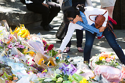 © Licensed to London News Pictures. 26/04/2016. London, UK.  A woman places a rose being handed out by members of the 1000RosesLondon group on London Bridge a week after a terror attack killed eight people. The group hopes to promote love and solidarity. Photo credit: Cliff Hide/LNP