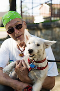 HOT SPRINGS, AR – JUNE 29, 2013: Don Jordan stops to pose with his dog while walking in a residential neighborhood.