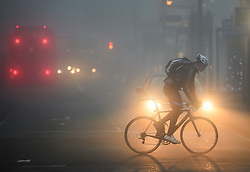 © Licensed to London News Pictures. 22/12/2016. London, UK. A cyclist makes his way along Ealing Broadway in West London, in thick fog on a cold winter morning. Temperatures over the upcoming Christmas period are expected to be unusually warm. Photo credit: Ben Cawthra/LNP