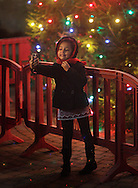 Middletown, NY - A young girl takes a photograph of herself in front of the holiday tree in Festival Square on Nov. 27, 2009.