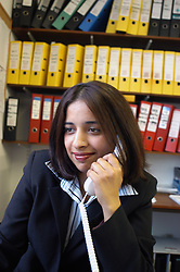 Female office worker talking on telephone; Halifax; Yorkshire UK