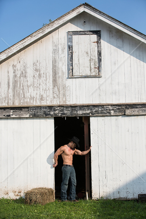muscular shirtless cowboy on a ranch with a rustic old barn