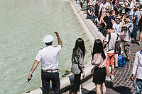 """ROME, ITALY - 20 JUNE 2017: A Roman policeman, entrusted to protect the Fountain of Trevi, order tourists to not sit on the edge of the fountain in Rome, Italy, on June 20th 2017.<br /> <br /> The warm weather has brought a menacing whiff of tourists behaving badly in Rome. On April 12, a man went skinny-dipping in the Trevi fountain resulting in a viral web video and a 500 euro fine.<br /> <br /> Virginia Raggi, the mayor of Rome and a national figurehead of the anti-establishment Five Star Movement,  issued an ordinance involving harsher fines for eating, drinking or sitting on the fountains, for washing animals or clothes in the fountain water or for throwing anything other than coins into the water of the Trevi Fountain, Bernini's Four Fountains and 35 other city fountains of artistic or historic significance around the city.  """"It is unacceptable that someone use them to go swimming or clean themselves, it's an historic patrimony that we must safeguard,"""" Ms. Raggi said."""