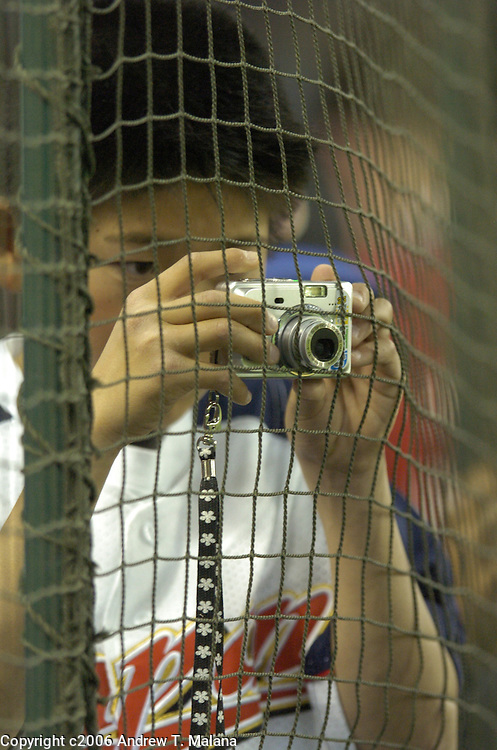 A young Team Japan fan pokes his camera through the netting to get the shot of his favorite players before the start of the second game of the World Baseball Classic at Tokyo Dome, Tokyo, Japan.